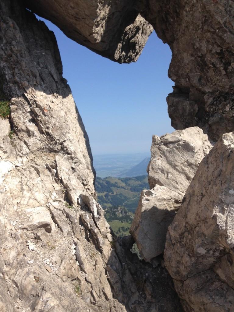 Ein Blick durch ein Felstor auf das Allgäuer Umland